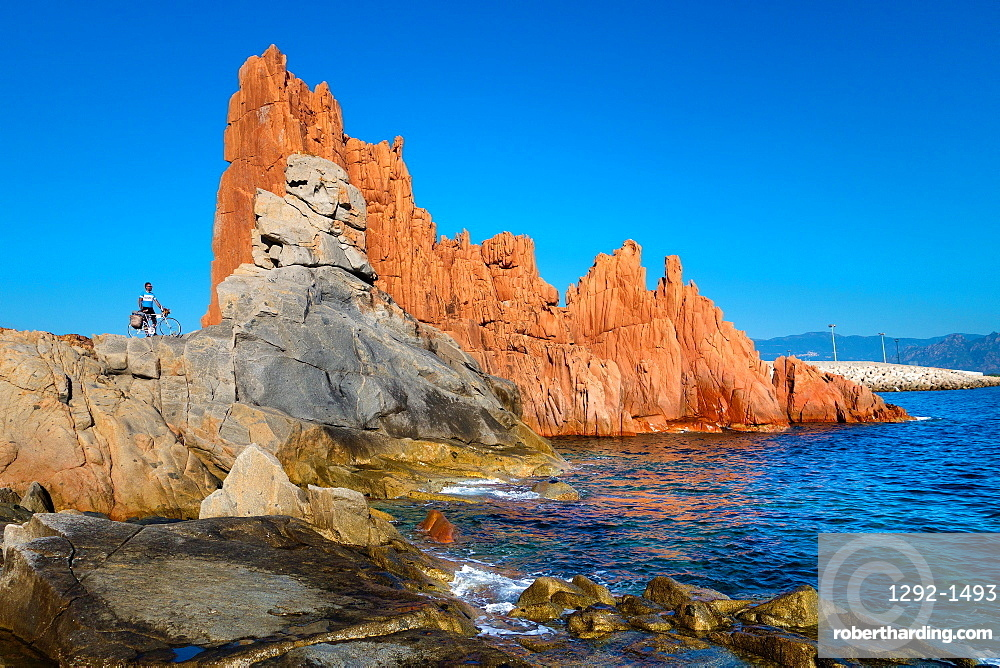 Man with bicycle on rocks by sea in Arbatax, Sardinia, Italy, Europe