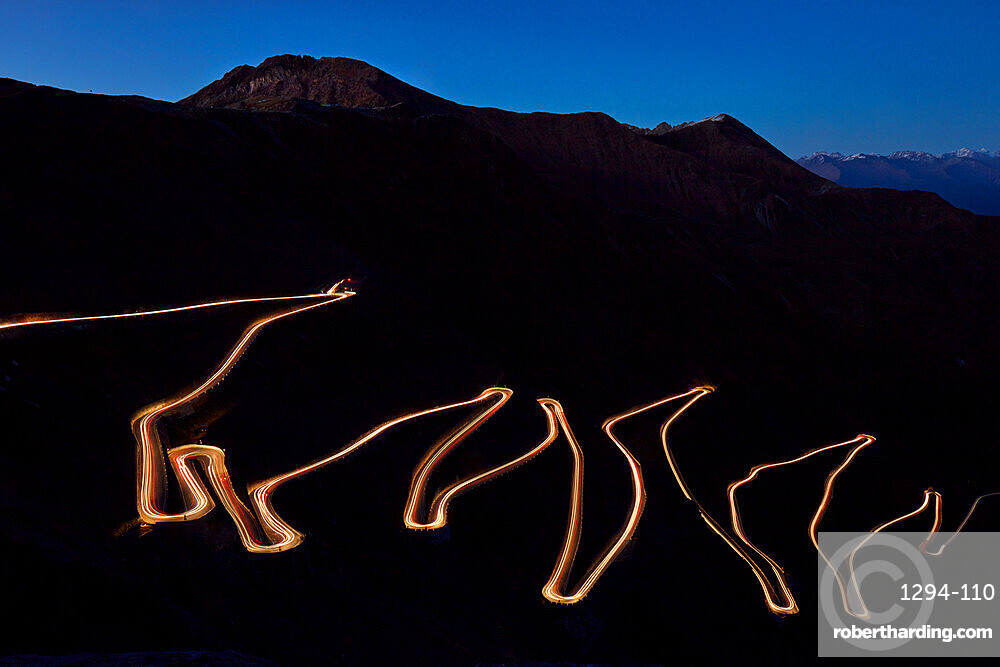 Pass road Stilfser Joch at night with light band of driving cars. Long time exposure