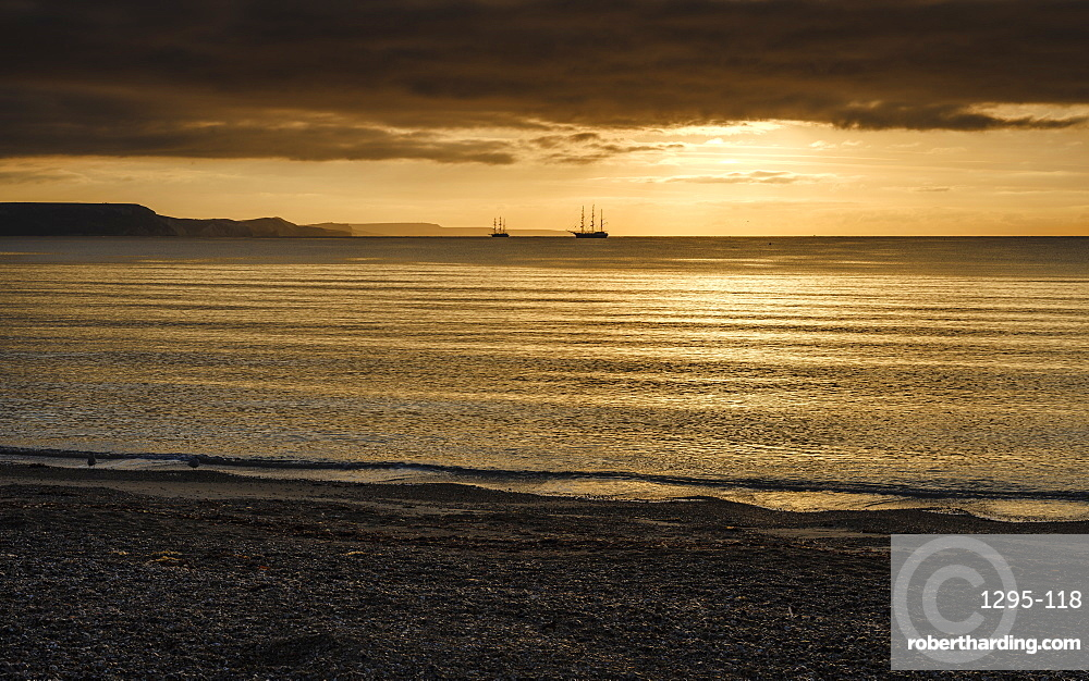 Two square rigger sailing vessels at anchor on a shimmering sea, adjacent to the Jurassic Cliffs, Weymouth, Dorset, England, United Kingdom, Europe
