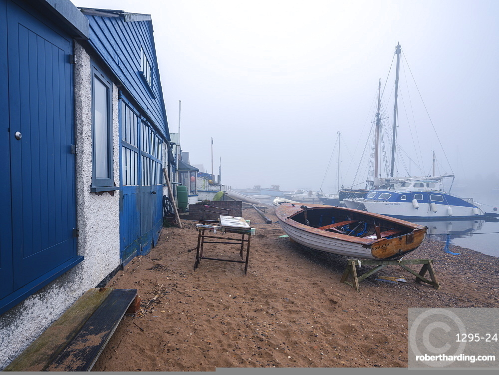 Misty scene with boats on the shoreline near the boatyard and sailmaker on a creek in Exmouth, Devon, England, United Kingdom, Europe
