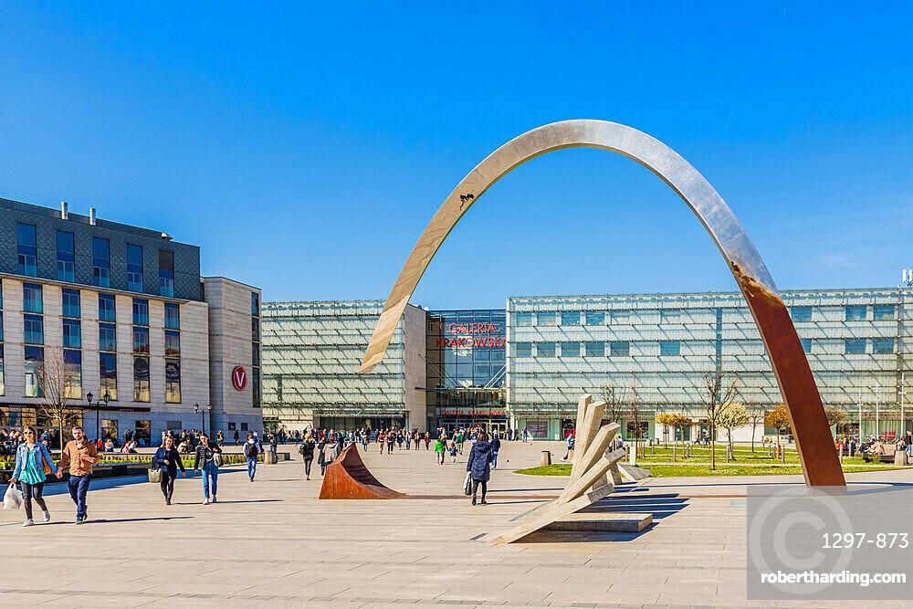 The Pomnik Ryszarda Kuklińskiego w Krakowie sculpture and the Galeria Krakowska Shopping centre mall in Krakow, Poland, Europe.