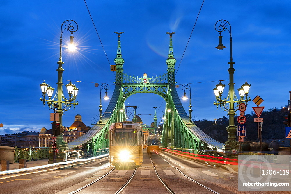 Trams crossing Liberty Bridge illuminated at night with the Gellert Hotel in the background, Budapest, Hungary, Europe