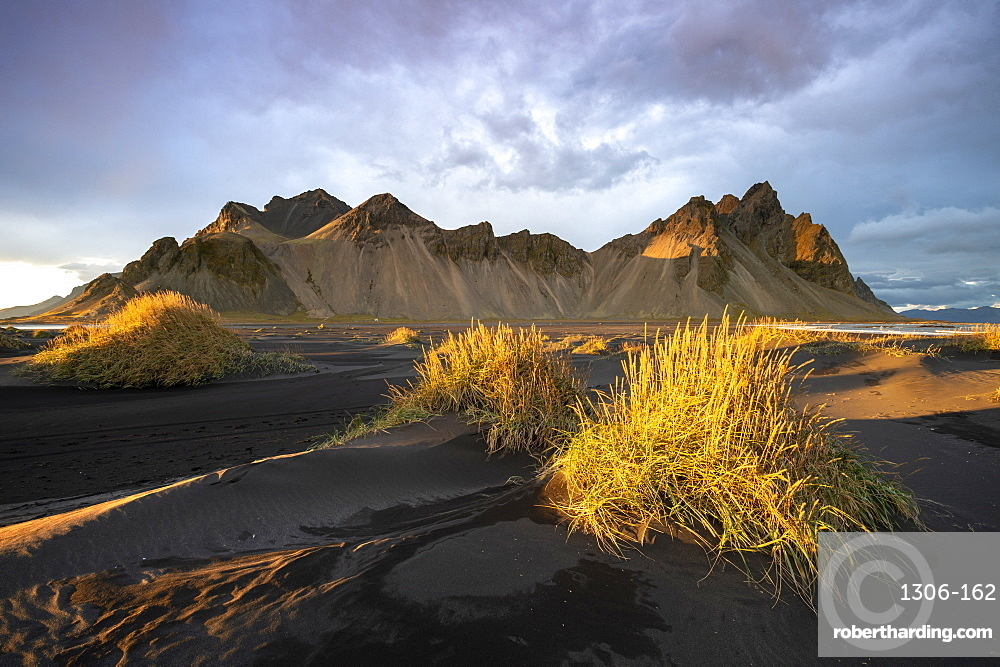 The view of the mountains of Vestrahorn from black volcanic sand beach with grasses at sunset, Stokksnes, South Iceland, Iceland, Polar Regions
