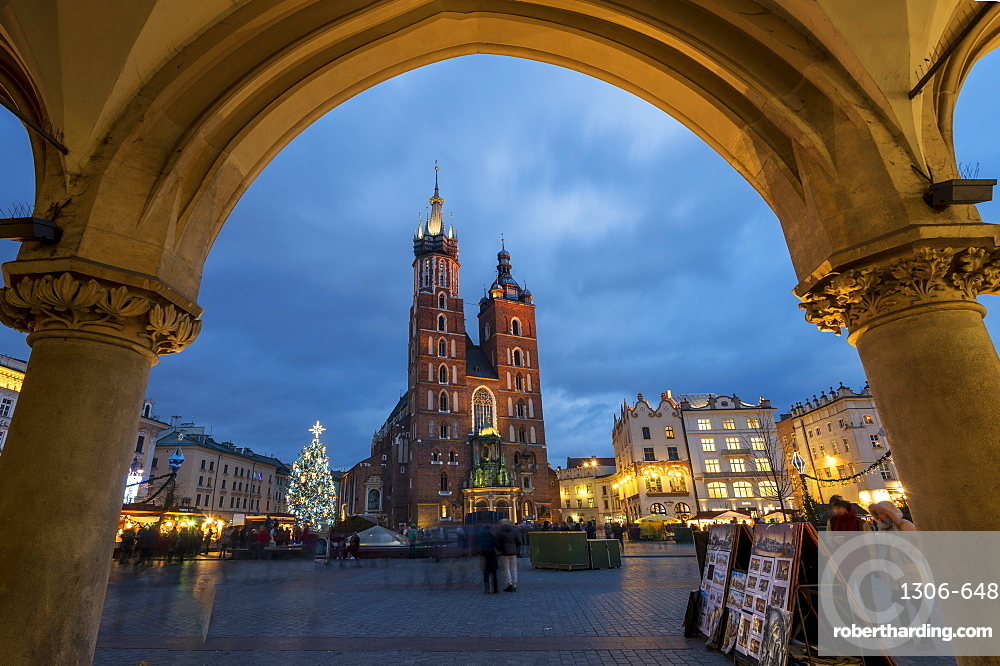 Saint Mary's Basilica at night framed with arch stonework in Market Square, Krakow, Poland