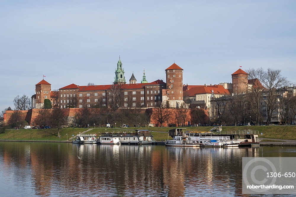 View to Wawel castle with restaurant boats moored on Wista River in riverside park. Krakow, Poland,