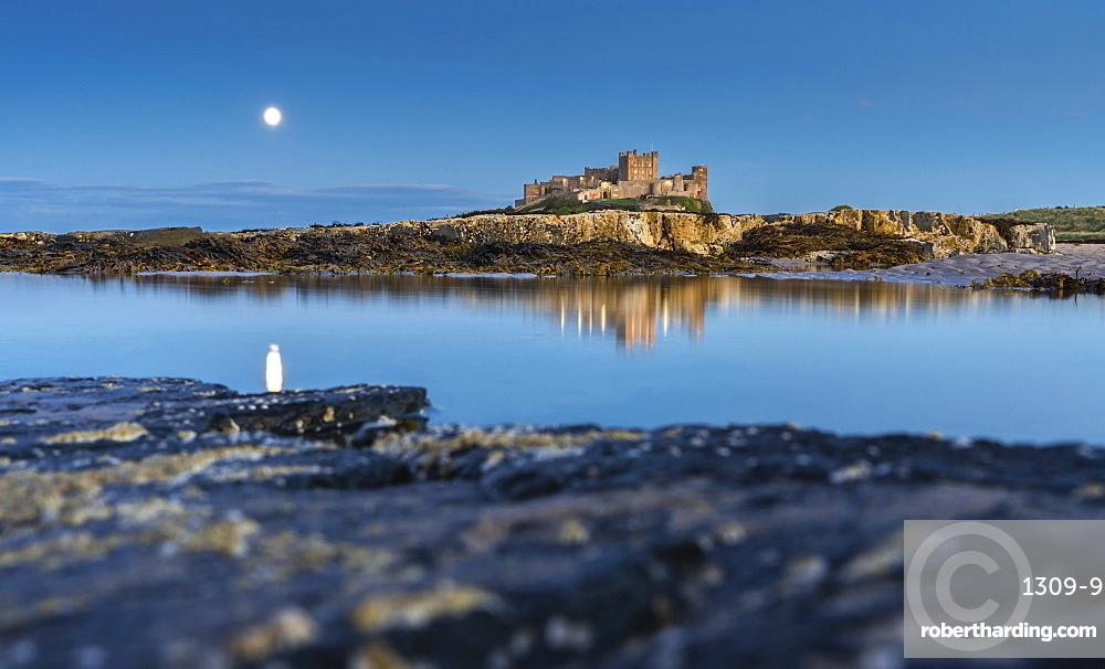 Moonlit Bamburgh Castle reflected in still water at dusk, Bamburgh, Northumberland, England, United Kingdom, Europe