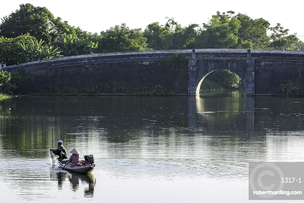 A man and woman fishing from a small boat in the moat around the Citadel in Hue