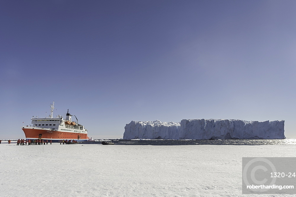 Large Iceberg and expedition ship against sea ice. Antarctica