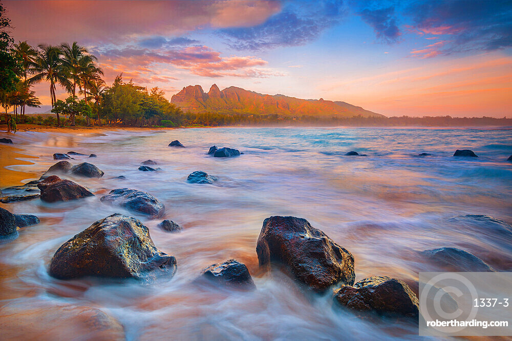 Sunrise over the calm bay waters at Anahola Beach Park, Kalalea mountain in the distance, Hawaii, United States of America, North America