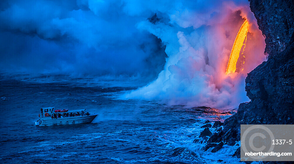 A tour boat observes lava pouring into the sea from 60 feet above as steam plumes billow up, Hawaii Volcanoes National Park, UNESCO World Heritage Site, Hawaii, United States of America, Pacific