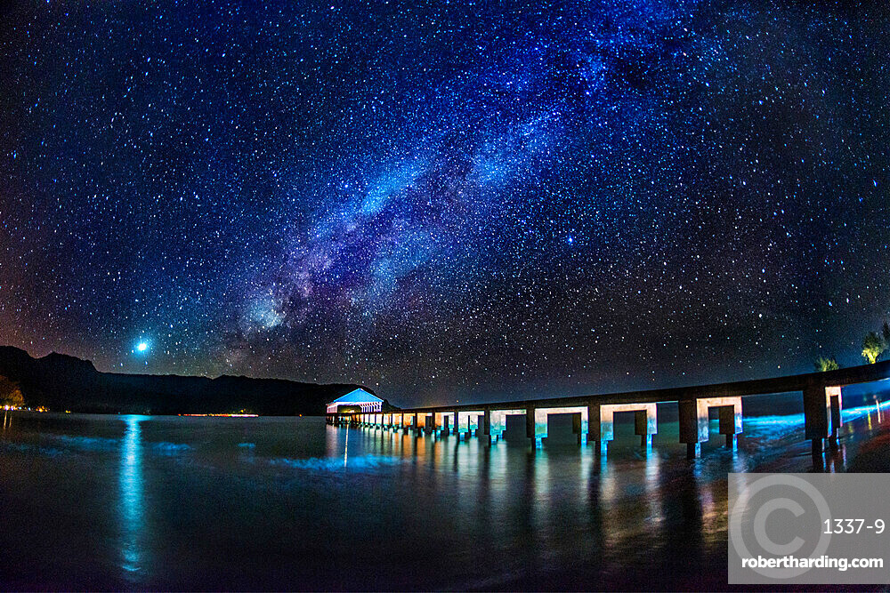 The Milky Way and Venus rise over the Hanalei Bay with the Hanalei Pier in the foreground lit by passing car headlights, Hanalei, Hawaii, United States of America, Pacific