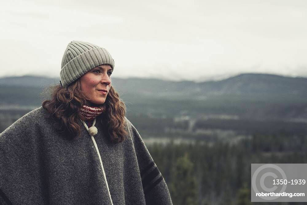 A 30 year old brunette lets her view wander above the valley. Yukon Territory, Canada