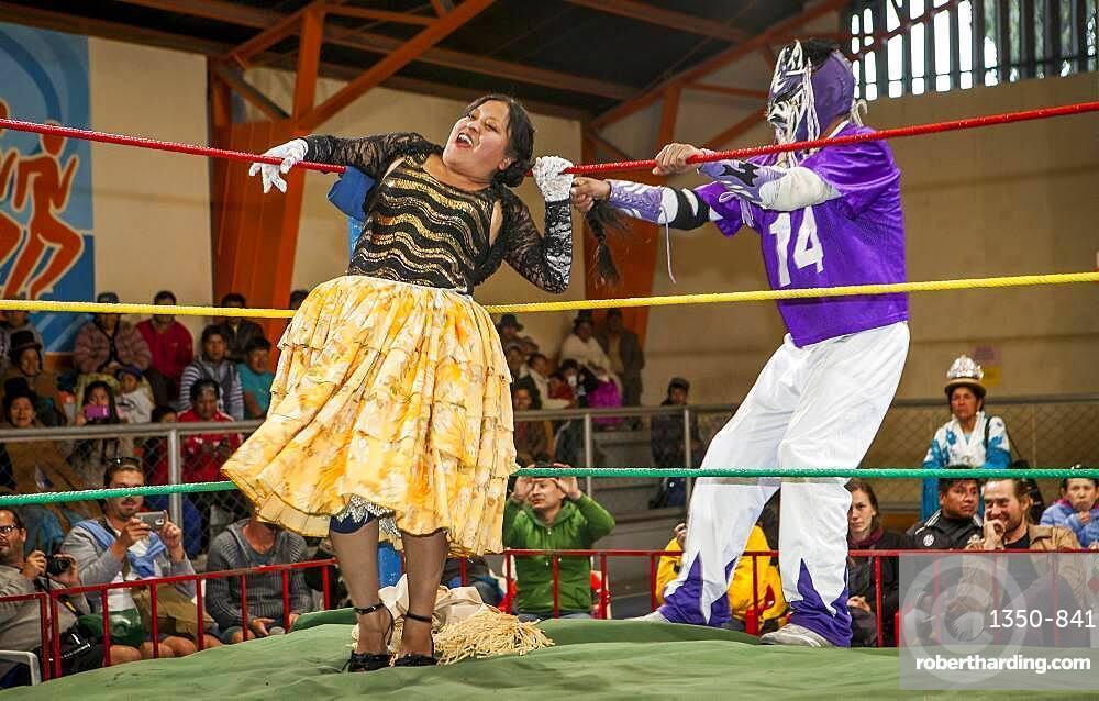 Lucha Libre. Male fighter stretch the hair of cholita Julieta, wrestlers in combat, Sports center La Ceja, El Alto, La Paz, Bolivia
