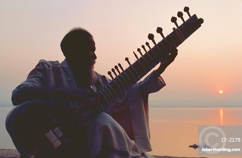 Elderly man playing the sitar beside the Ganges (Ganga) River, Varanasi (Benares), Uttar Pradesh State, India