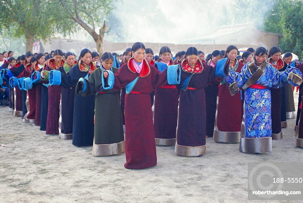Tibetan women pray at Harvest Festival, Tongren Area, Qinghai Province, China