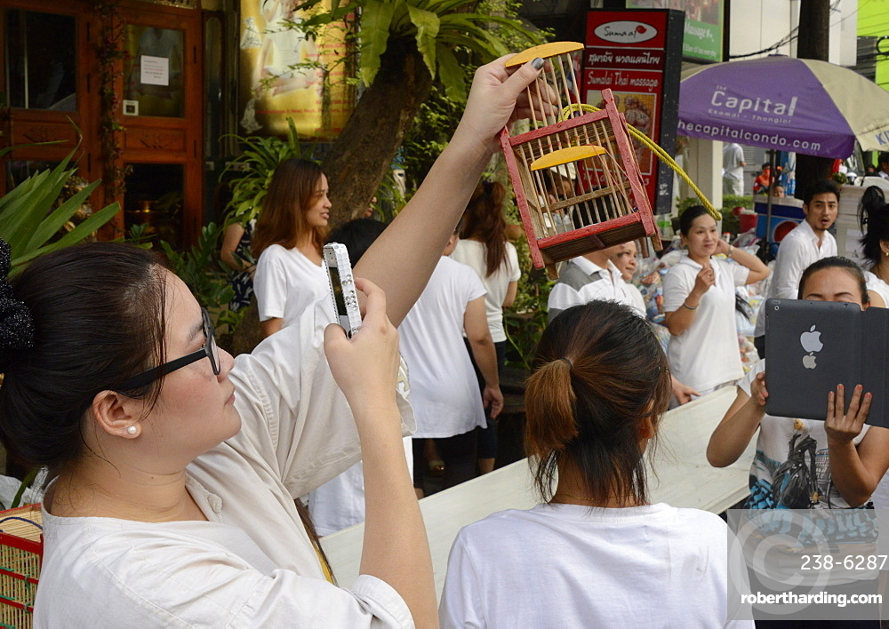 Releasing of birds to gain merit, another facebook opportunity, Bangkok, Thailand, Southeast Asia, Asia