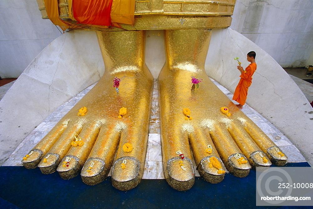 Novice monk praying at the feet of Giant Buddha statue, Wat Intharawihan (Wat In), Bangkok, Thailand, Asia
