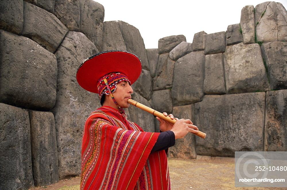 Portrait of a Peruvian man playing a flute, Inca ruins of Sacsayhuaman, near Cuzco, Peru, South America