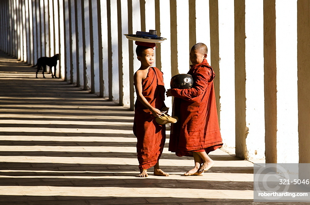 Novice Buddhist monks collecting alms, standing in the shadows of columns at Shwezigon Paya, Nyaung U, Bagan, Myanmar (Burma), Asia