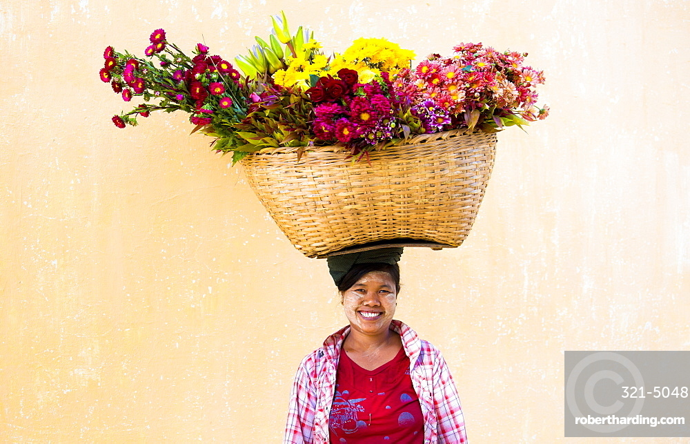 Local woman with thanakha traditional face painting, carrying a large basket of fresh flowers on her head, Shwezigon Paya, Nyaung U, Myanmar (Burma), Asia