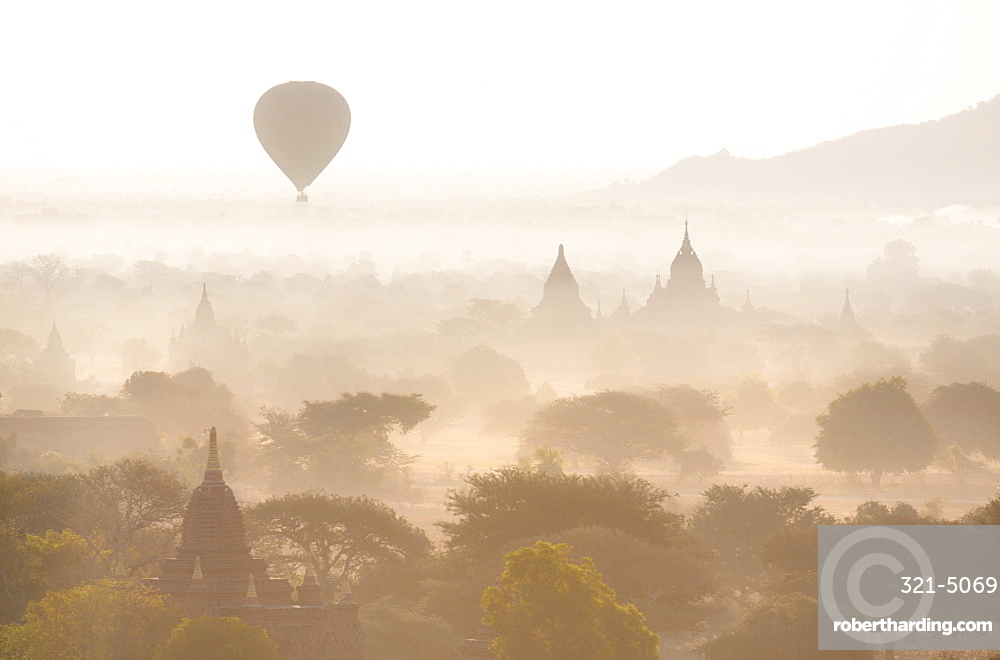View over the temples of Bagan swathed in early morning mist, with hot air balloon drifting across the scene, from Shwesandaw Paya, Bagan, Myanmar (Burma), Southeast Asia