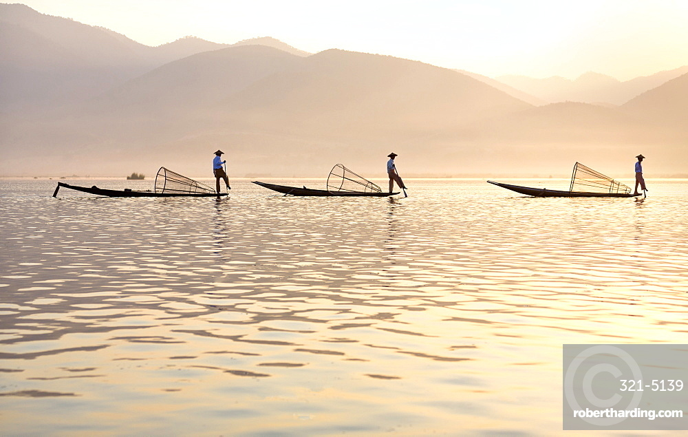 Intha 'leg rowing' fishermen at sunset on Inle Lake who row traditional wooden boats using their leg and fish using nets stretched over conical bamboo frames, Inle Lake, Myanmar (Burma), Southeast Asia