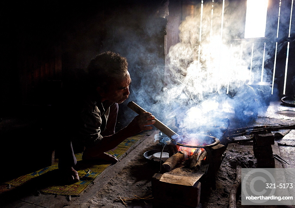 Man of the Palaung tribe cooking on open fire in his home in village near Kengtung (Kyaingtong), Shan State, Myanmar (Burma), Asia