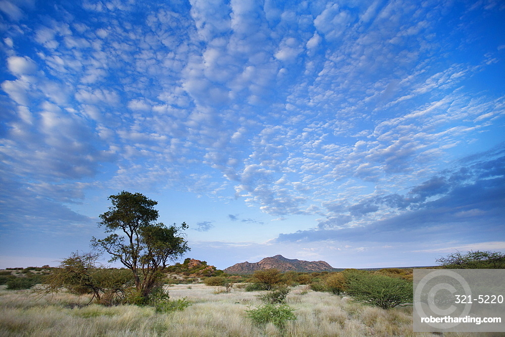 Early morning view across barren landscape towards sandstone mountains beneath dramatic sky, near Spitzkoppe, Namibia, Africa