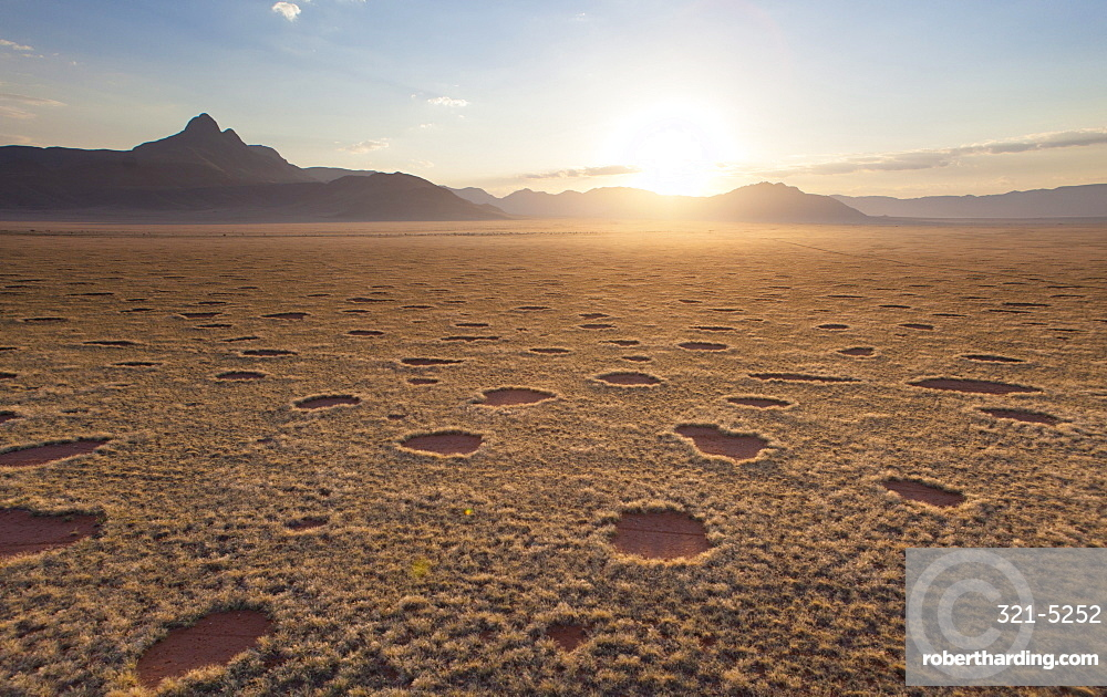 Aerial view from hot air balloon at dawn over magnificent desert landscape of sand dunes, mountains and Fairy Circles, Namib Rand game reserve Namib Naukluft Park, Namibia, Africa