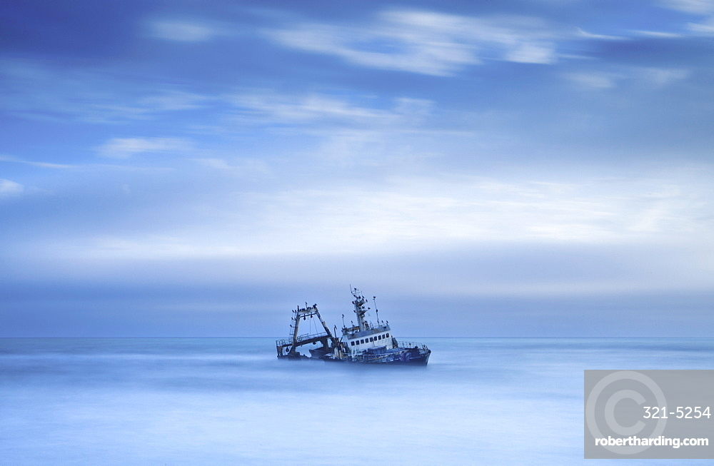 Shipwreck off the Atlantic coast, shot with long exposure to record motion in sea and sky, near Walvis Bay, Namibia, Africa