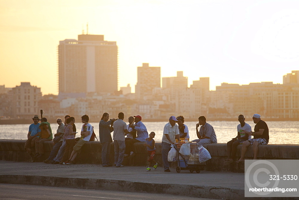 Local people sat on the sea wall at sunset, with buildings of Havana in the background, The Malecon, Havana Centro, Havana, Cuba, West Indies, Central America
