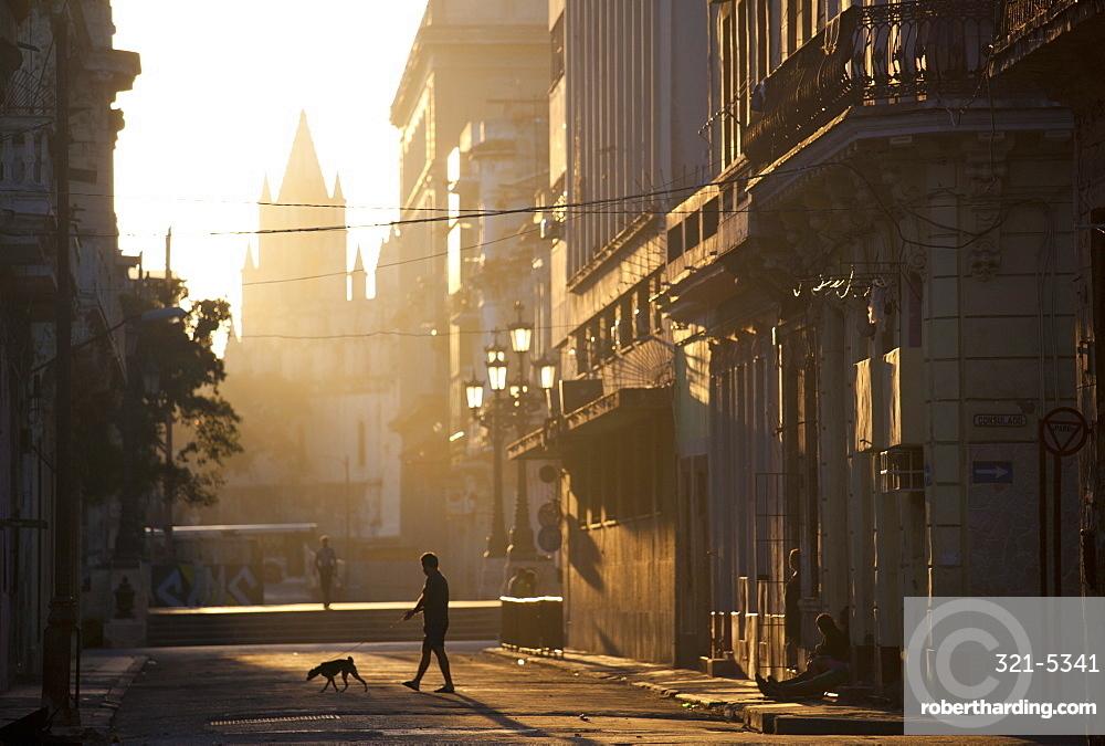 Backlit street at dawn with people in semi-silhouette, off Prado, Havana Centro, Havana, Cuba, West Indies, Central America