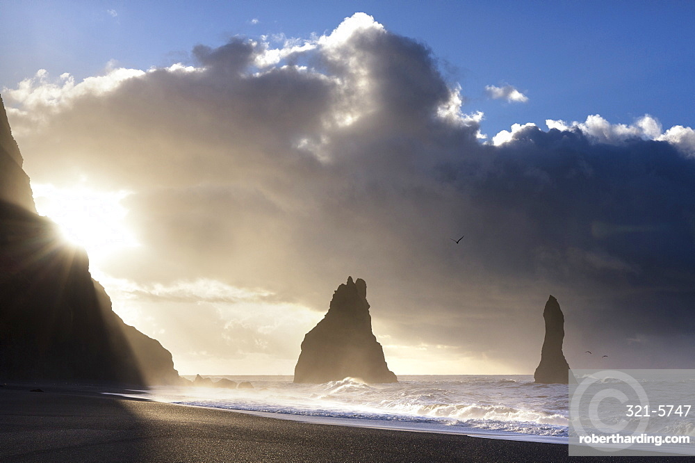 Rock stacks of Reynisdrangar in silhouette at sunrise, from Halsanefs Hellir Beach, near Vik Y Myrdal, South Iceland, Polar Regions