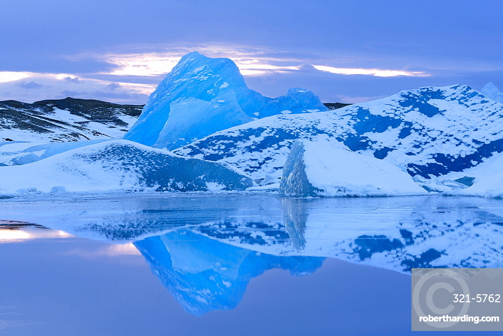 Icebergs covered in dusting of snow, winter, sunset, Jokulsarlon Glacial Lagoon, South Iceland, Polar Regions
