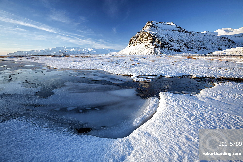 Snow covered landscape in winter with frozen pool, mountain and Vatnajokull Glacier, near Jokulsarlon Lagoon, South Iceland, Polar Regions