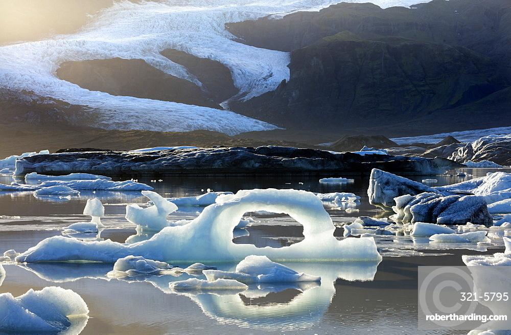 Ice arch among icebergs floating on Fjallsarlon lagoon, near Jokulsarlon, South Iceland, Polar Regions