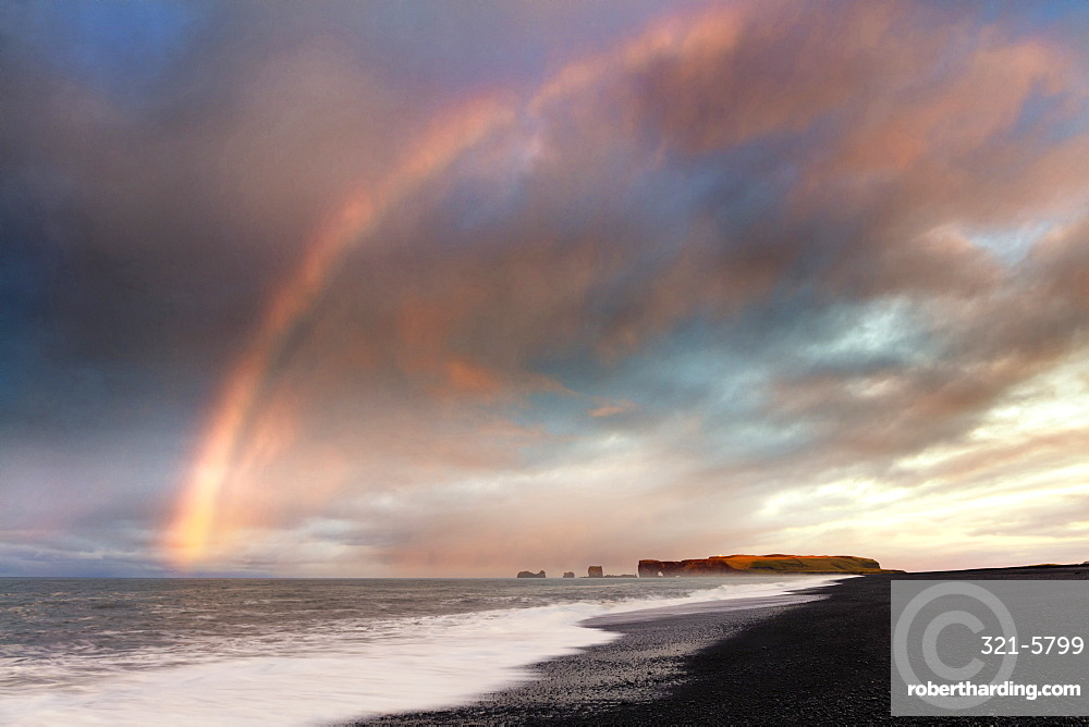 Distant view of Dyrholaey at sunrise with rainbow, from Halsanefs Hellir Beach near Vik, South Iceland, Polar Regions