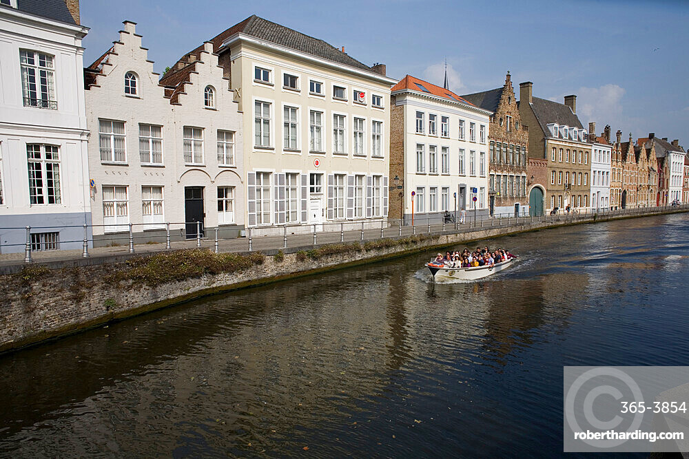 Spinolarei canal with builidings on Sint-Annarei and approaching boat carrying tourists, Bruges, Belgium