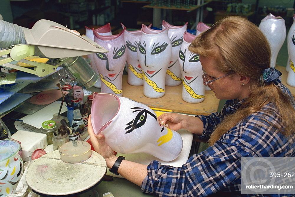 Kosta Boda artist paints features of vase in artist's collection, Kosta, Sweden, Scandinavia, Europe