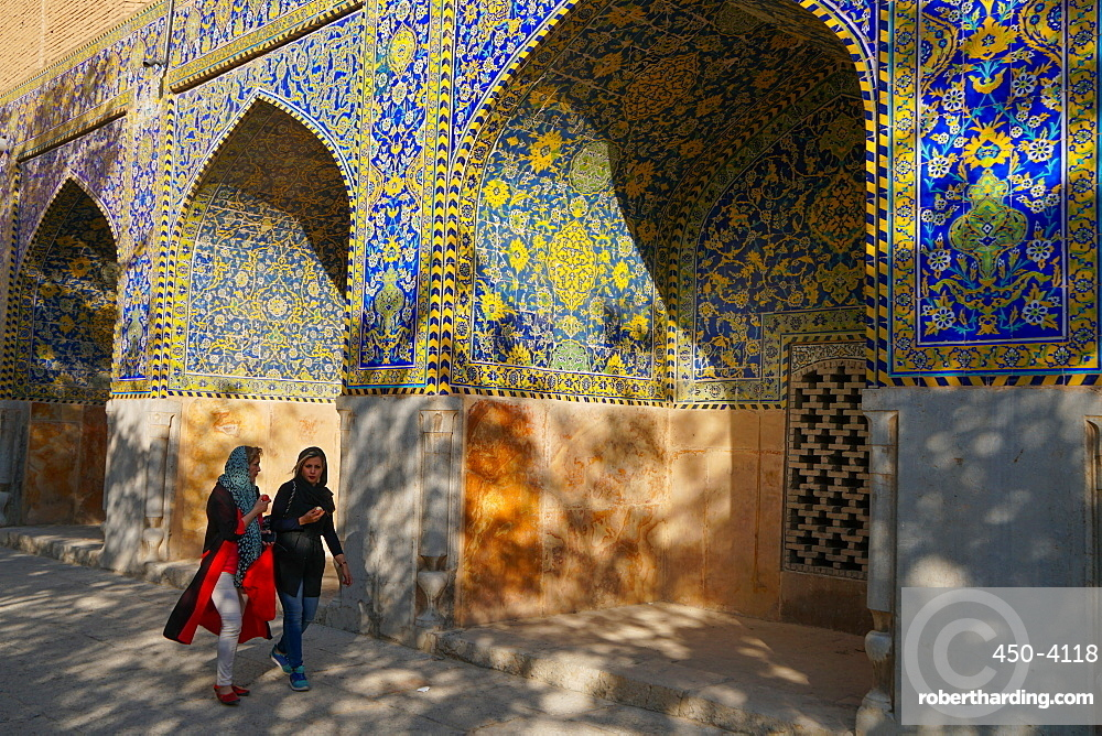 Two Iranian girls walking past courtyard walls, Imam Mosque, UNESCO World Heritage Site, Isfahan, Iran, Middle East