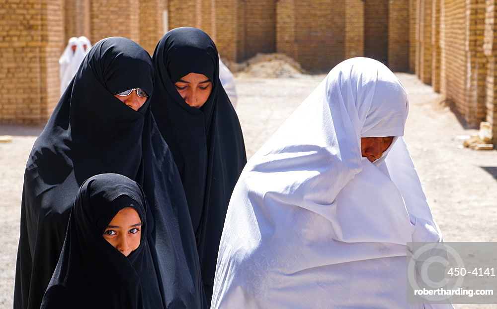 Different generations, different outlooks, grandmother in less common white chador and women and granddaughter in black chadors, Varzaneh, Iran, Middle East