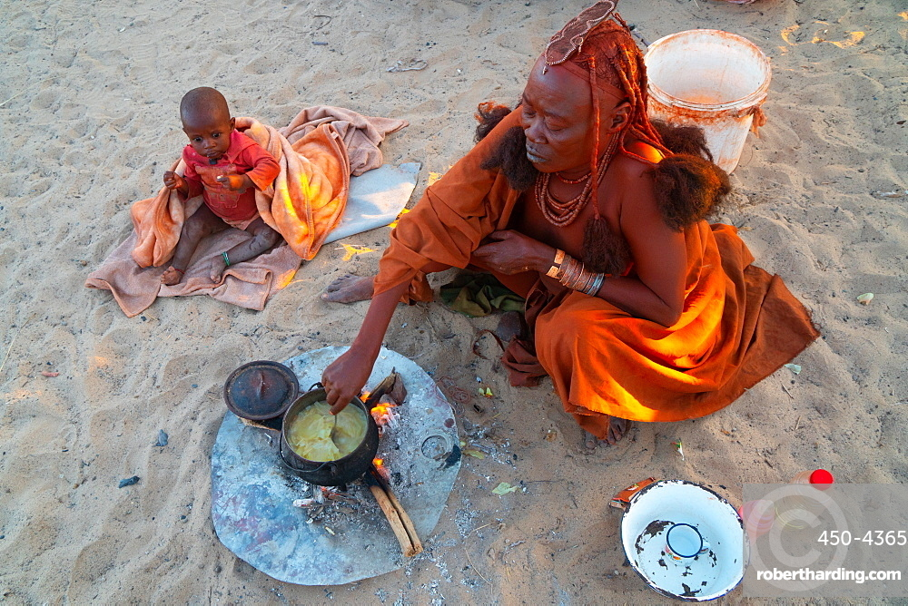 One senior red ochred Himba woman with her child cooking on an open fire, Puros Village, nearr Sesfontein, Namibia, Africa