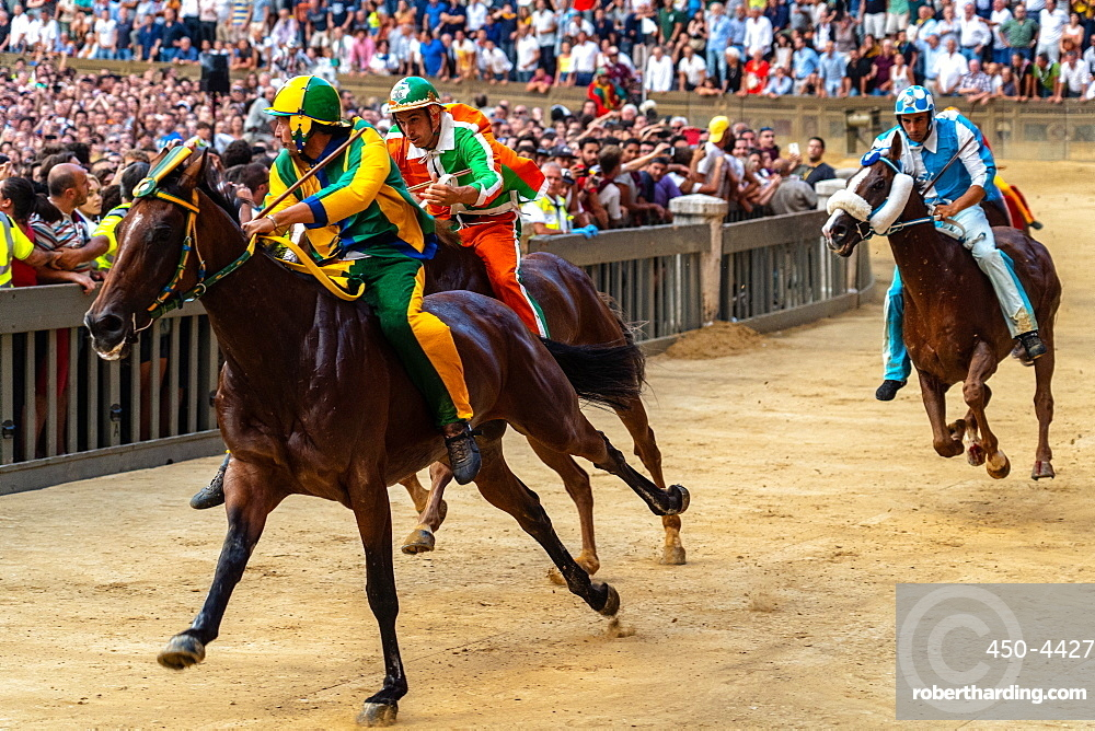 Jockeys in colourful outfits representing their respective neighbourhoods (contrade) vying for the lead at the Palio, Siena, Tuscany, Italy, Europe