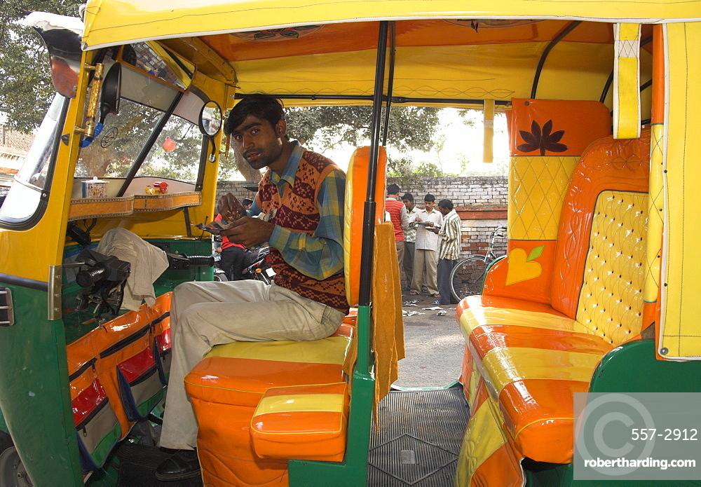 Rickshaw owner sitting in his newly decorated moto rickshaw, Agra, Uttar Pradesh state, India, Asia