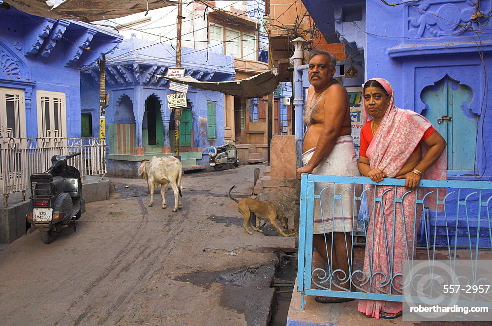 Couple standing outside blue painted residential haveli, Old City, Jodhpur, Rajasthan state, India, Asia