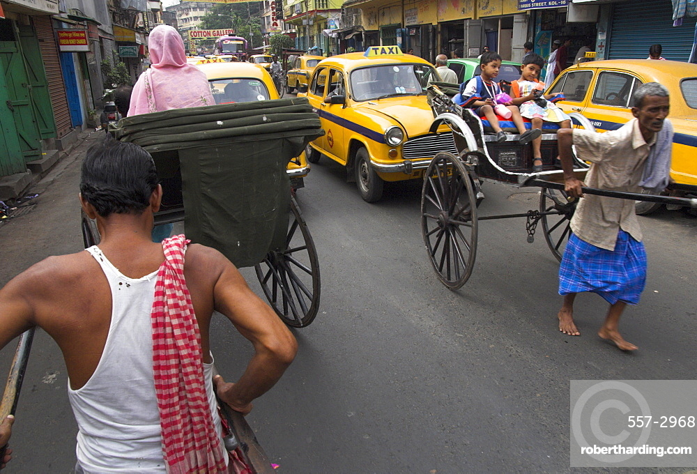 Hand pulled rickshaws and yellow taxis, Kolkata, West Bengal state, India, Asia