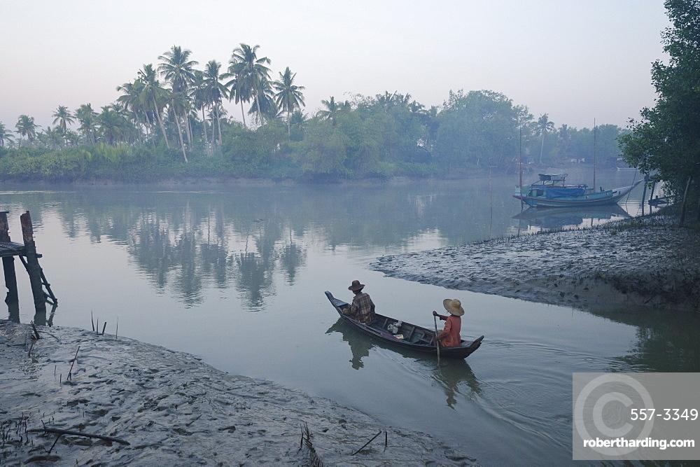 Two women on a small boat in early morning light, Oak Po Kwin Chaung village, Irrawaddy Delta, Myanmar (Burma), Asia