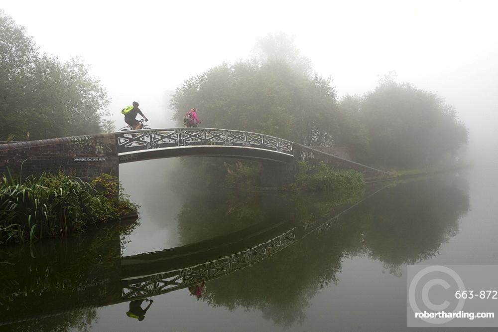 A cyclist on a bridge on Birmingham Canal Navigations (BCN), Birmingham, West Midlands, England, United Kingdom, Europe