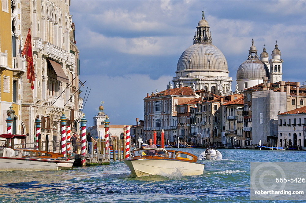 Taxi and boat on Grand Canal with palace facades and Salute church domes, San Marco, Venice, UNESCO World Heritage Site, Veneto, Italy, Europe