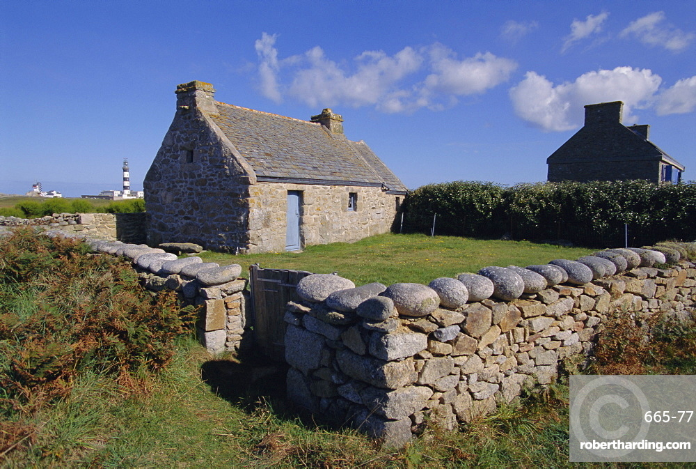Ancient house with Creac'h lighthouse behind on Ouessant Island, Brittany, France, Europe